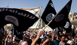 Demonstrators chant pro-Islamic State group slogans as they wave the group's flags in front of the provincial government headquarters in Mosul, Iraq, in this Monday, June 16, 2014, file photo. (AP Photo, File)