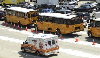 An ambulance rushes by congested traffic on the New Jersey side of the Lincoln Tunnel in Weehawken, N.J., Wednesday, June 10, 2015. A New Jersey transit bus rear-ended a private bus injuring at least 18 people at around 9:30 a.m. in the center tube on the New York side of the tunnel connecting it with New Jersey, according to a spokesman for the Port Authority of New York and New Jersey police. (AP Photo/Joe Epstein)