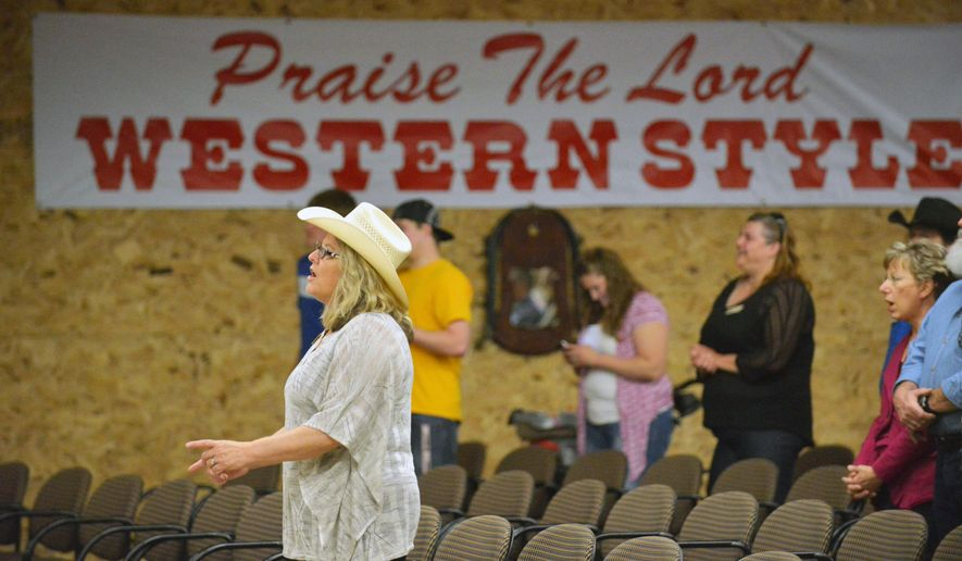 ADVANCE FOR WEEKEND EDITIONS JUNE 13-14 - In this May 31, 2015 photo, Linda Penrose, left, wife of Pastor Joe Penrose, worships with others at the Open Range Cowboy Church in Ham Lake, Minn. Even in the most liberal translations, the Bible doesn't mention 10-gallon hats or roping cattle. Nevertheless, Minnesota's first cowboy-themed church is thriving in Ham Lake. (Scott Takushi/The St. Paul Pioneer Press via AP)  MINNEAPOLIS STAR TRIBUNE OUT