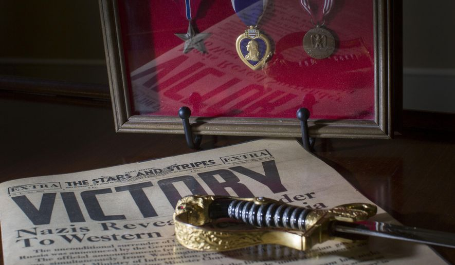 This June 4, 2015 photo shows items that D-Day veteran William C. Scott brought home items from World War II, including a Stars And Stripes newspaper from May 8, 1945, and a Nazi soldier's sword in San Antonio, Texas.   Upon return, he received a Bronze Star, Purple Heart and Good Conduct Medal.   (Ray Whitehouse/The San Antonio Express-News via AP) RUMBO DE SAN ANTONIO OUT; NO SALES