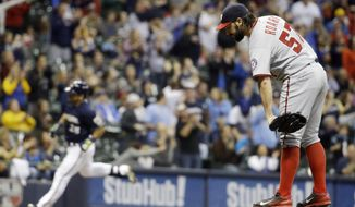 Washington Nationals starting pitcher Tanner Roark, right, gets a new ball as Milwaukee Brewers' Gerardo Parra rounds the bases after Parra hit a home run during the seventh inning of a baseball game Thursday, June 11, 2015, in Milwaukee. (AP Photo/Morry Gash)
