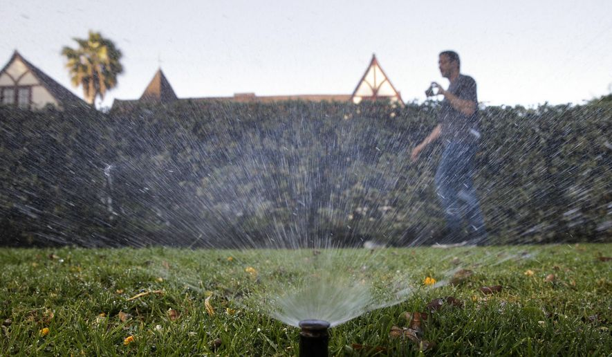 In this Friday, June 5, 2015, photo, Tony Corcoran records sprinklers watering the lawn in front of a house in Beverly Hills, Calif. Corcoran is one of several people who spend their spare time these days canvassing the tony communities of Beverly Hills, West Hollywood and elsewhere, looking for people wasting water during the worst California drought in recent memory. (AP Photo/Jae C. Hong)