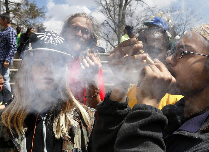 In this April 18, 2015 photo, young partygoers listen to music and smoke marijuana during the annual 4/20 marijuana festival, in Denver's downtown Civic Center Park. (AP Photo/Brennan Linsley) ** FILE **