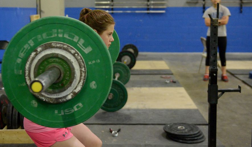 ADVANCED FOR RELEASE SUNDAY, JUNE 14, 2015 Abigail Henderson, 11, trains during Alamance Barbell Club's practice at KaiJax Gym in Gibsonville, N.C. Monday June 8, 2015. (Sam Roberts/Burlington Times-News via AP)