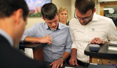 Mitch Fortune, left, and Jake Crouch look over paperwork before applying for a marriage license at the Buncombe County Register of Deeds office in Asheville, N.C., Tuesday, Oct. 15, 2013. (AP Photo/Adam Jennings)