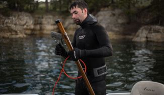 In this photo taken on Saturday, June 6, 2015, a competitor emerges from the water with his custom-made spear gun during the U.S. Freshwater Spearfishing Nationals at Keyhole Reservoir near Moorcroft, Wyo. (Ryan Dorgan/The Casper Star-Tribune via AP)