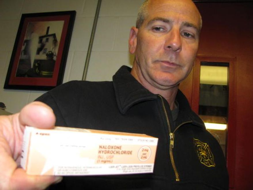 In this photo taken June 1, 2015, Marion Fire Department Capt. Wade Ralph shows a dose of naloxone, used by emergency crews to revive overdosing heroin users in Marion, Ohio. The life-saving drug was used repeatedly when a super-charged batch of heroin led to more than 30 overdoses in an 11-day period at the end of May in the small Ohio city. (AP Photo/Mitch Stacy)