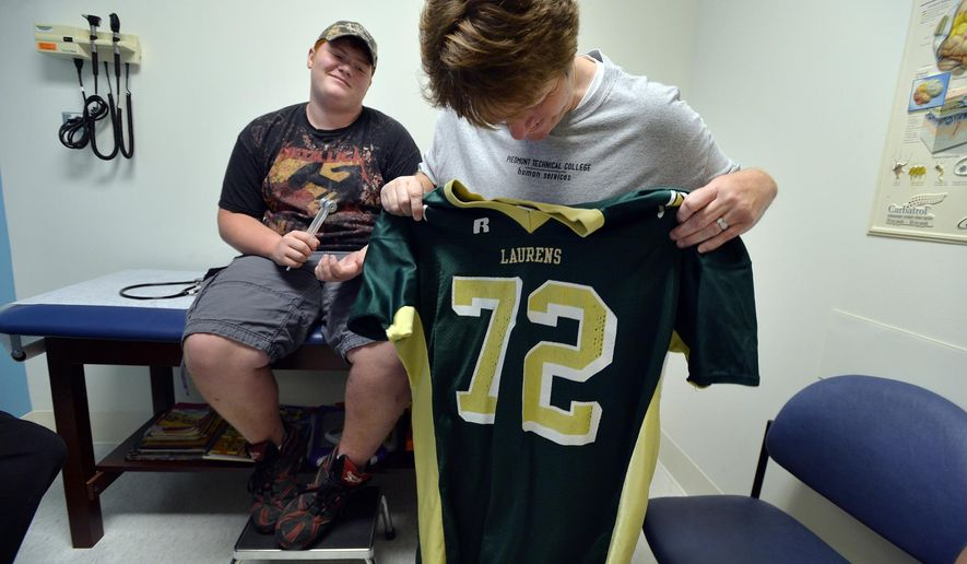ADVANCED FOR RELEASE SUNDAY, JUNE 14, 2015 Kimberley Lovejoy holds up the football uniform of son Jacob Lovejoy, a 16-year-old stroke survivor, progress during a checkup visit on Wednesday, May 27, 2015. (Mykal McEldowney/The Greenville News via AP) MANDATORY CREDIT NO SALES