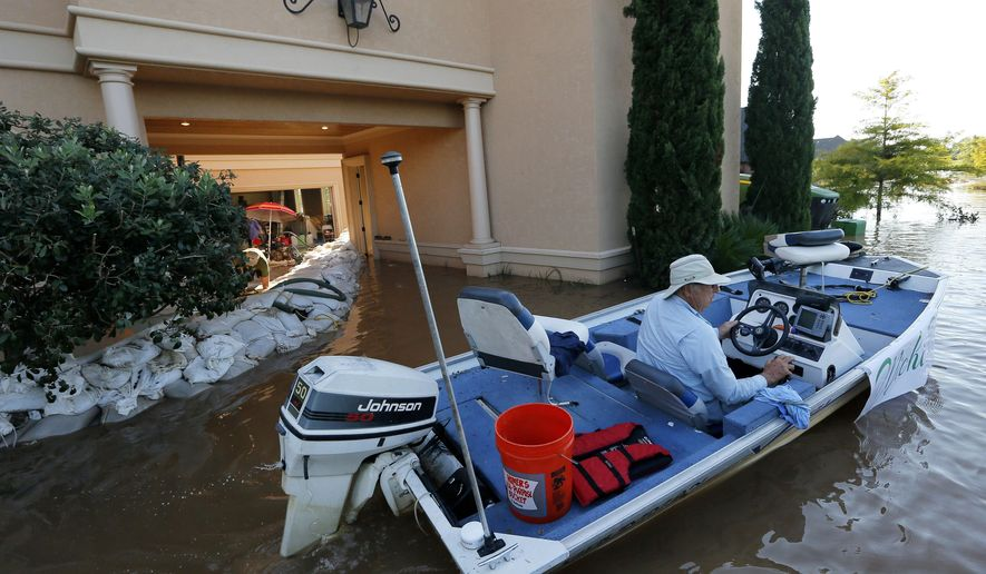 Rigby Hollingsworth boats past a family friend's home that is protected by sandbags from water caused by the flooding of the Red River, Wednesday, June 10, 2015, in Bossier City, La. (AP Photo/Jonathan Bachman)