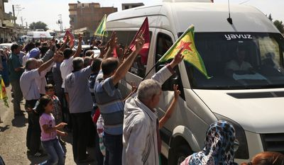 Kurdish people waving flags flash the V-sign and applaud while lining the road, as the convoy carrying the body of U.S. citizen Keith Broomfield, killed in fighting with the militants of the Islamic State group in Kobani, Syria, is driven by through Suruc, on the Turkey-Syria border, Thursday, June 11, 2015. (AP Photo/Lefteris Pitarakis)