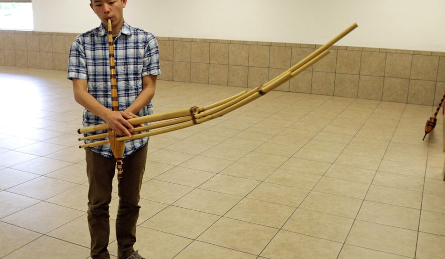 In this photo taken on Wednesday, June 3, 2015, Jason Yang, 17, practices his Qeej technique at the Hmong Cultural Center, in Sheboygan, Wisc. (Gary C. Klein/The Sheboygan Press via AP) NO SALES