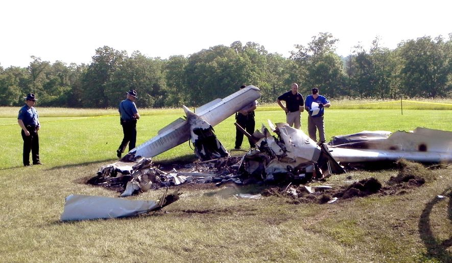 In this photo provided by The Houston Herald, authorities investigate a plane crash Friday, June 12, 2015 near Huggins, Mo. Authorities say C. Mark Openshaw, 43 a Utah State Board of Education member, his wife and two of their children died and another child was hurt when their small plane crashed while taking off from a relative's grass airstrip. The family was returning to their Provo, Utah, home after visiting relatives. (Doug Davison/Houstonherald.com via AP) MANDATORY CREDIT