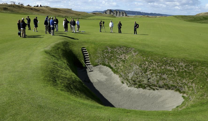 In this Sept. 30, 2014, photo, reporters and photographers stand near the deep pot bunker on the 18th fairway at Chambers Bay, the host course for the 2015 U.S. Open golf tournament, in University Place, Wash. (AP Photo/Ted S. Warren)