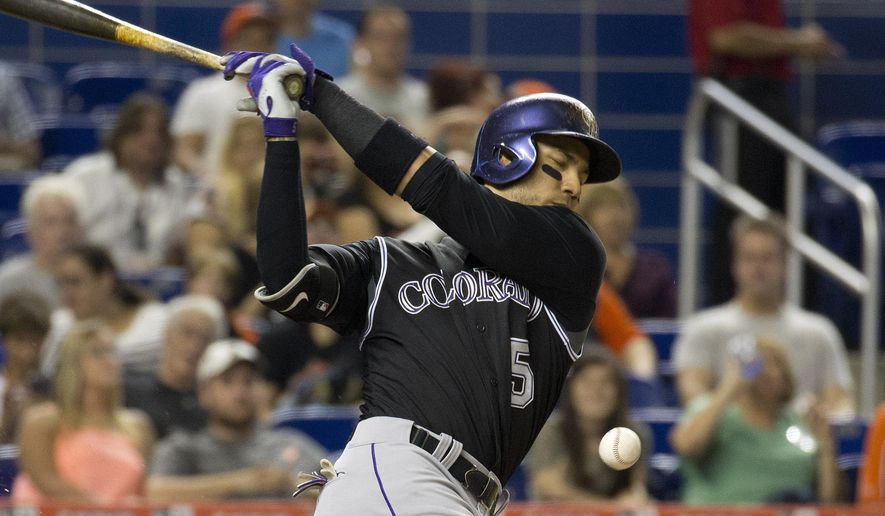 Colorado Rockies' Carlos Gonzalez (5) hits a foul ball during the second inning of a baseball game against the Miami Marlins in Miami, Friday, June 12, 2015. (AP Photo/J Pat Carter)
