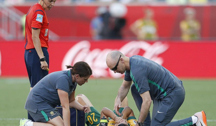 Medical staff tend to Australia's Samantha Kerr (20) during FIFA Women's World Cup second-half soccer game action in Winnipeg, Manitoba, Friday, June 12, 2015. (John Woods/The Canadian Press via AP) MANDATORY CREDIT