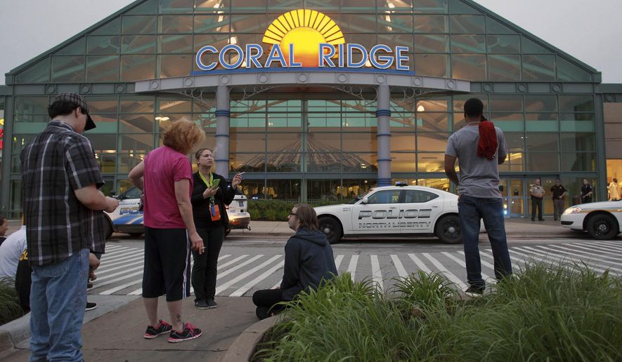 Shoppers and employees wait outside the Coral Ridge Mall following a shooting on Friday, June 12, 2015 in Coralville, Iowa. A spokesman for Iowa Gov. Terry Branstad  says a suspect is in custody and the public is not believed to be in further danger. He says more information will be released soon. (David Scrivner/Iowa City Press-Citizen via AP)  NO SALES
