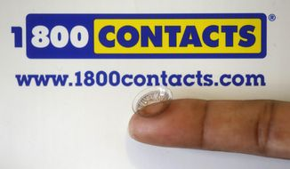 FILE - In this May 13, 2015 file photo, a contact lens is shown in front of a 1-800 Contacts shipping box in Salt Lake City. A federal appeals court will allow a hotly contested Utah law banning price fixing for contact lenses to go into effect.  The decision handed down Friday, June 12, 2015 from the 10th Circuit Court of Appeals in Denver comes after three of the nation's largest contact lens manufacturers sued to block the measure. The law could have wide-ranging effects on the roughly $4 billion contact lens market, which has some 38 million American consumers. (AP Photo/Rick Bowmer, File)