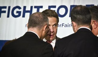 New York Gov. Andrew Cuomo, second from left, speaks with officials at rally for Fight for Fair Pay wage campaign, Thursday, June 11, 2015, in New York. As search continues for two escaped convicts, Gov. Cuomo said tracking dogs had picked up their scent. (AP Photo/Bebeto Matthews)