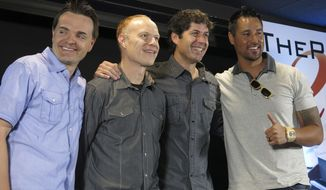 Band members of The Piano Guys, from left to right, Steven Sharp Nelson, cellist; Jon Schmidt, pianist; Paul Anderson, videographer and Al van der Beek, music producer, pose for pictures during a press conference to promote their upcoming concert in Mexico City, Tuesday, July 30, 2013. (AP Photo/Isaac Garrido)
