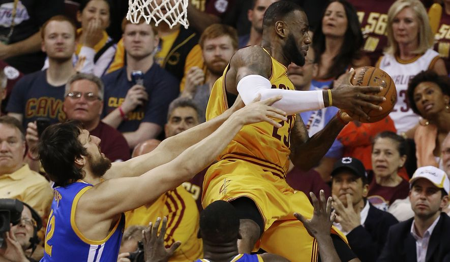 Cleveland Cavaliers forward LeBron James (23) is hit by Golden State Warriors center Andrew Bogut (12) during the first half of Game 4 of basketball's NBA Finals in Cleveland, Thursday, June 11, 2015. James injured his head on the play. (AP Photo/Paul Sancya)