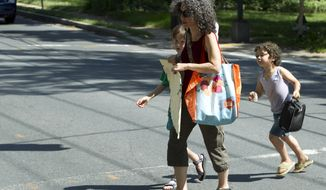 """Danielle Meitiv walks home with her children Rafi, 10, left and Dvora, 6, right, after picking them up at the school bus stop in Silver Spring Md., on Friday, June 12, 2015. After outcry over one family's """"free-range"""" parenting case, Maryland officials on Friday clarified the state's policy on how authorities handle cases of children walking or playing alone outdoors, saying the state shouldn't investigate unless kids are harmed or face substantial risk of harm. (AP Photo/Jose Luis Magana)"""
