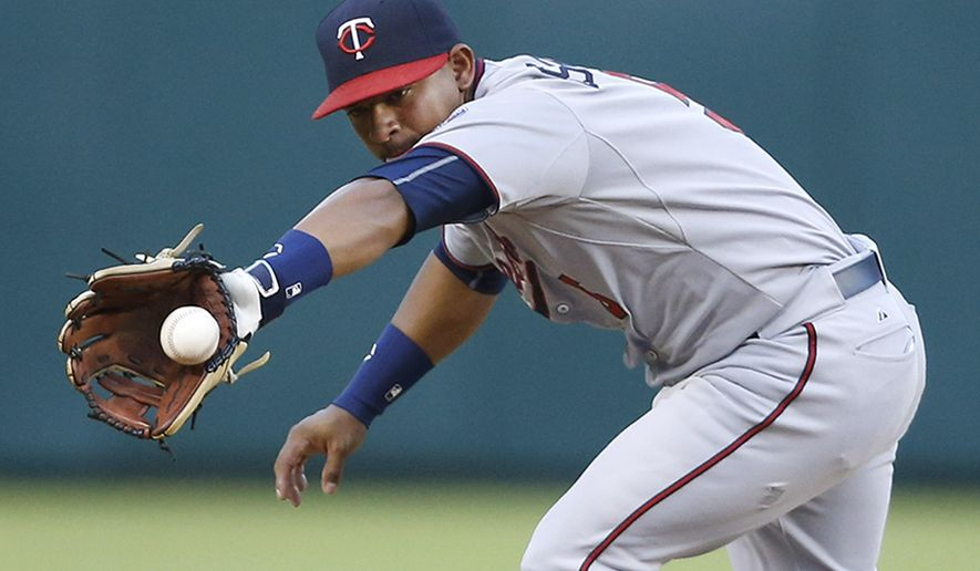 Minnesota Twins shortstop Eduardo Escobar fields a ball hit by Texas Rangers' Carlos Corporan in the fifth inning of a baseball game Friday, June 12, 2015, in Arlington, Texas. (AP Photo/Ron Jenkins)