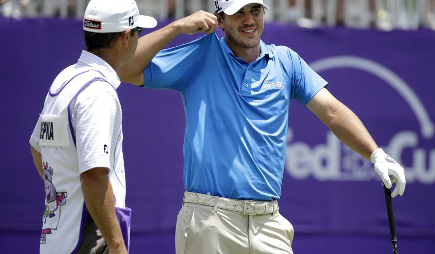 Brooks Koepka, right, loosens his shirt as he waits to tee off on the first tee during the second round of the St. Jude Classic golf tournament, Friday, June 12, 2015, in Memphis, Tenn. (AP Photo/Mark Humphrey)