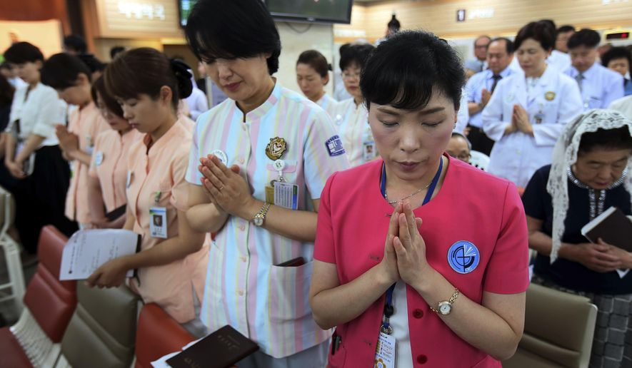 Hospital workers pray as they attend a special service for patients suffering from MERS, Middle East Respiratory Syndrome, at a Sungmo hospital in Seoul, South Korea, Friday, June 12, 2015. The outbreak of Middle East respiratory syndrome has caused panic in South Korea. (Park Ji-ho/Yonhap via AP) KOREA OUT