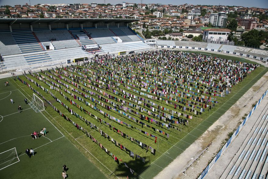 Rows of women's clothing hang, as a part of an art installation called 'Thinking of You' by Kosovo born artist Alketa Xhafa Mripa, in Pristina Stadium, Kosovo, Friday, June 12, 2015. Thousands of dresses and skirts were collected and hung across the field of the Pristina stadium, in a tribute to the estimated 20,000 wartime sexual violence survivors from Kosovo's 1998-1999 war for independence from Serbia. (AP Photo/Visar Kryeziu)