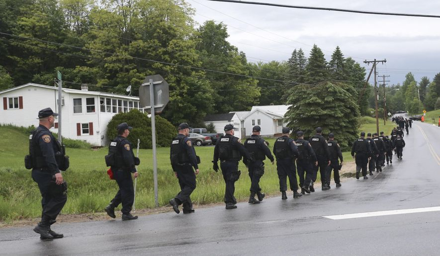 Law enforcement officers walk along Route 3 and Trudeau Road after emerging from the woods during a search for two escapees from Clinton Correctional Facility on Friday, June 12, 2015, near Dannemora, N.Y. Squads of law enforcement officers are searching for David Sweat and Richard Matt, two murderers who escaped from the maximum-security prison in northern New York. (AP Photo/Mike Groll)