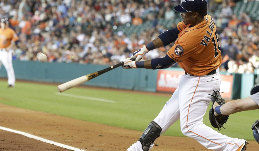 Houston Astros' Luis Valbuena swings on a three-run home run against the Seattle Mariners during the first inning of a baseball game Friday, June 12, 2015, in Houston. (AP Photo/Pat Sullivan)