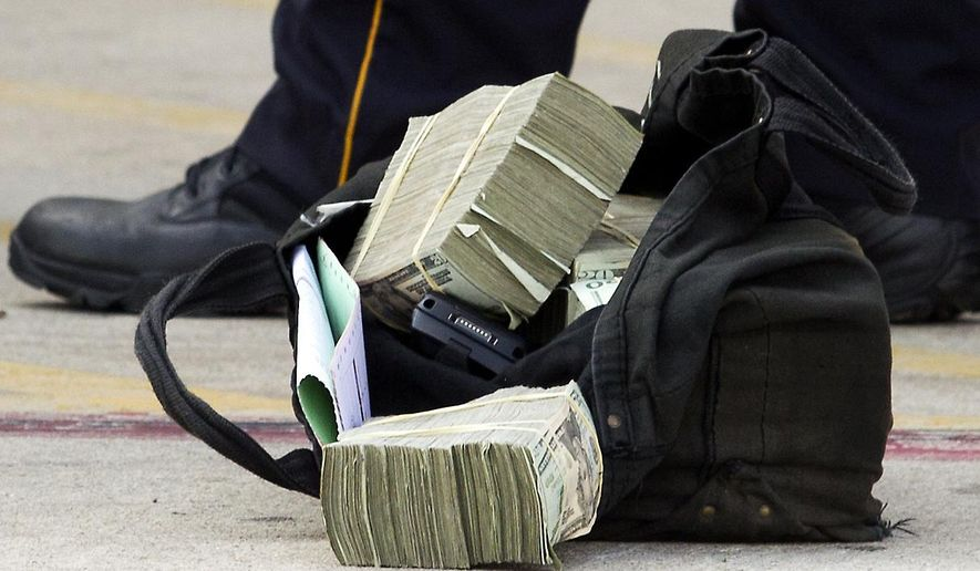 In this Sept. 6, 2013 photo, a  bag of money is left in a parking lot after an armored car was robbed off of Little York and the Eastex freeway in Houston.  Eleven armored trucks were robbed in Houston in 2013 and another eight last year, accounting for 20 percent of all such heists in the U.S. In 2013, 120 banks were robbed around Houston, one every three days. Last year the number dipped slightly to 100, while nearly 4,000 banks, savings and loans and credit unions were held up nationwide, according to FBI statistics.  ( J. Patric Schneider/Houston Chronicle via AP)  MANDATORY CREDIT