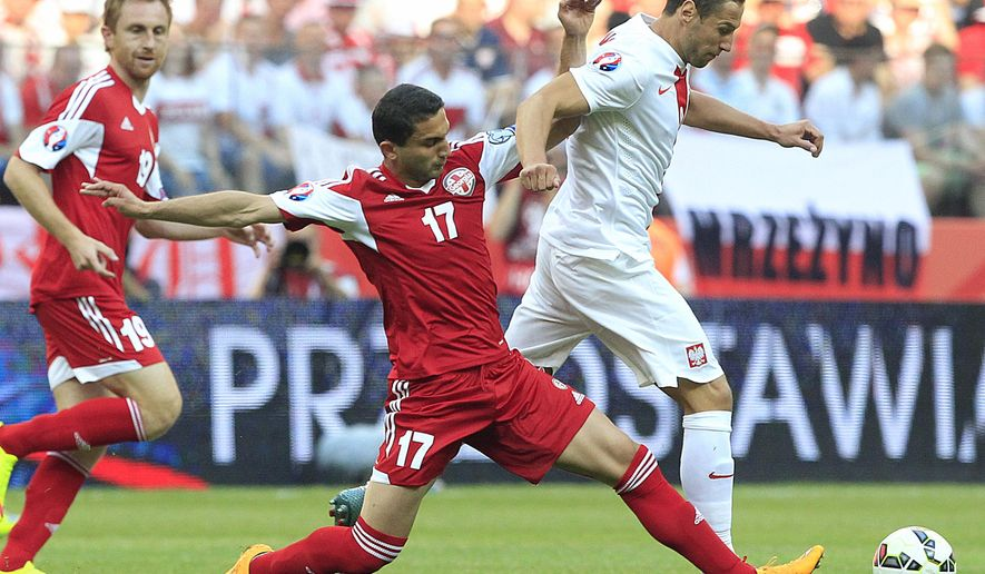 Poland's Lukasz Szukala, right, fights for the ball with Georga's Aleksandre Kabakhidze, left, and Mate Vatsadze, center, during the Euro 2016 qualifying match between Poland and Georgia, at the National stadium, in Warsaw, Poland, Saturday, June 13, 2015. (AP Photo/Czarek Sokolowski)