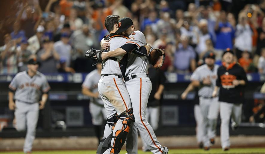 San Francisco Giants pitcher Chris Heston, right, hugs Buster Posey as teammates run to them after Heston threw a no-hitter against the New York Mets in a baseball game Tuesday, June 9, 2015, in New York. The Giants won 5-0. (AP Photo/Frank Franklin II)