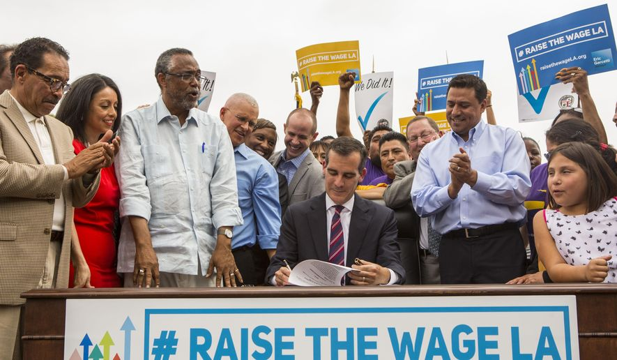 Los Angeles Mayor Eric Garcetti, center, joins members of the City Council and community leaders as he signs into law an ordinance that will gradually raise the minimum wage to $15 an hour by 2020, in at Martin Luther King Jr. Park in Los Angeles, Saturday, June 13, 2015. The ordinance makes Los Angeles the largest city in the U.S. to gradually raise the minimum wage to $15 an hour. (AP Photo/Ringo H.W. Chiu)