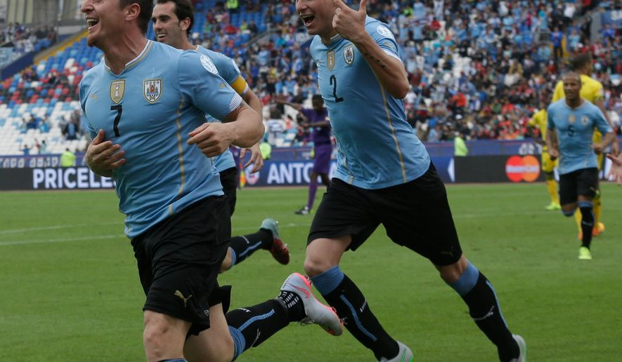 Uruguay's Cristian Rodriguez, left, celebrates with teammates after scoring  during a Copa America Group B soccer match at the Calvo y Bascunan Regional Stadium in Antofagasta, Chile, Saturday, June 13, 2015. (AP Photo/ Luis Hidalgo)