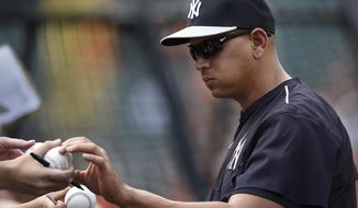 New York Yankeed' Alex Rodriguez autographs baseball before the Yankees' baseball game against the Baltimore Orioles, Saturday, June 13, 2015, in Baltimore. (AP Photo/Gail Burton)