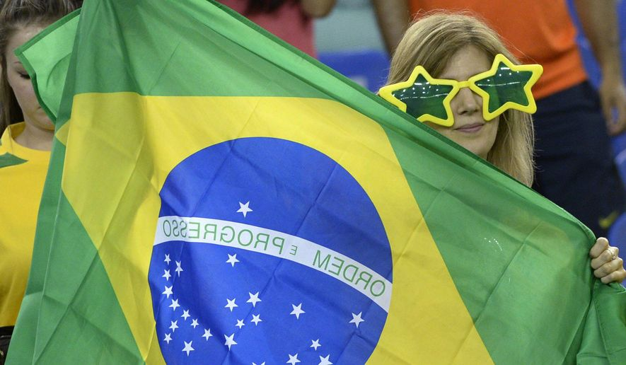 A Brazil fan holds a flag during FIFA Women's World Cup soccer action against Spain in Montreal on Saturday, June 13, 2015. (Paul Chiasson/The Canadian Press via AP) MANDATORY CREDIT