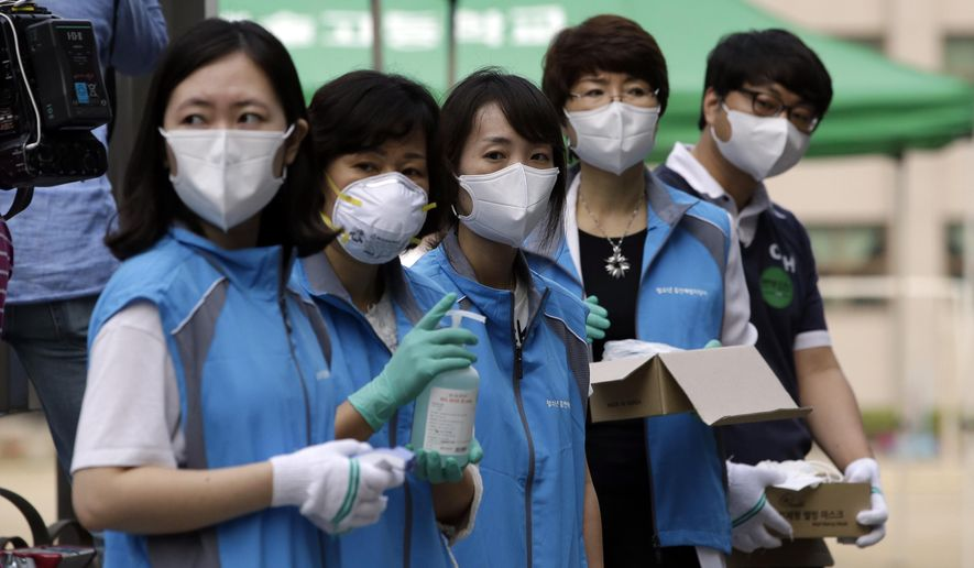 South Korean health workers from a community health center wearing masks as a precaution against MERS, Middle East Respiratory Syndrome, virus, wait to check examinees' temperature and to sanitzie their hands at a test site for a civil service examination in Seoul, South Korea, Saturday, June 13, 2015. Experts from the World Health Organization and South Korea have downplayed concerns about the MERS virus spreading further within the country, but they say it's premature to declare the outbreak over. (AP Photo/Lee Jin-man)