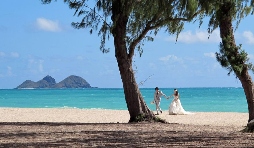 A couple from Japan takes wedding photos at Waimanalo Bay Beach Park, on Wednesday June 10, 2015, in Waimanalo, Hawaii. (AP Photo/Jennifer Sinco Kelleher) ** FILE **