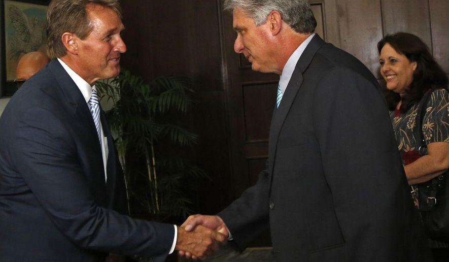 Sen. Jeff Flake, R-Ariz, shakes hands with Cuba's First Vice President Miguel Diaz Canel, at Revolution Palace, in Havana, Cuba, Saturday, June 13, 2015. (AP Photo/Desmond Boylan, Pool)