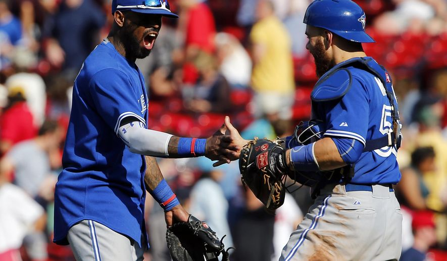 Toronto Blue Jays' Jose Reyes, left, celebrates with catcher Russell Martin after their 5-4 win over the Boston Red Sox in 11 innings during a baseball game at Fenway Park in Boston Saturday, June 13, 2015. (AP Photo/Winslow Townson)