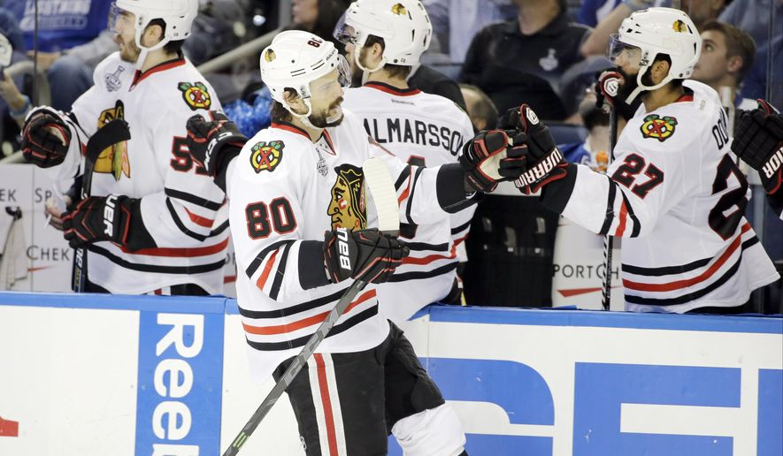 Chicago Blackhawks center Antoine Vermette (80) is congratulated by teammates after scoring against the Tampa Bay Lightning during the third period of Game 5 of the NHL hockey Stanley Cup Final, Saturday, June 13, 2015, in Tampa, Fla. (AP Photo/Chris O'Meara)
