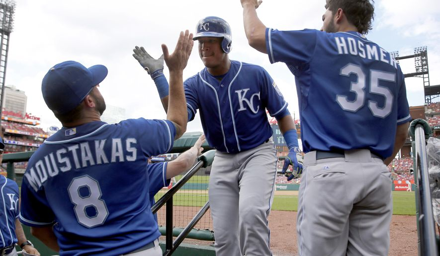 Kansas City Royals' Salvador Perez, center, is congratulated by teammates Mike Moustakas, left, and Eric Hosmer after hitting a solo home run during the fourth inning of a baseball game against the St. Louis Cardinals, Saturday, June 13, 2015, in St. Louis. (AP Photo/Jeff Roberson)