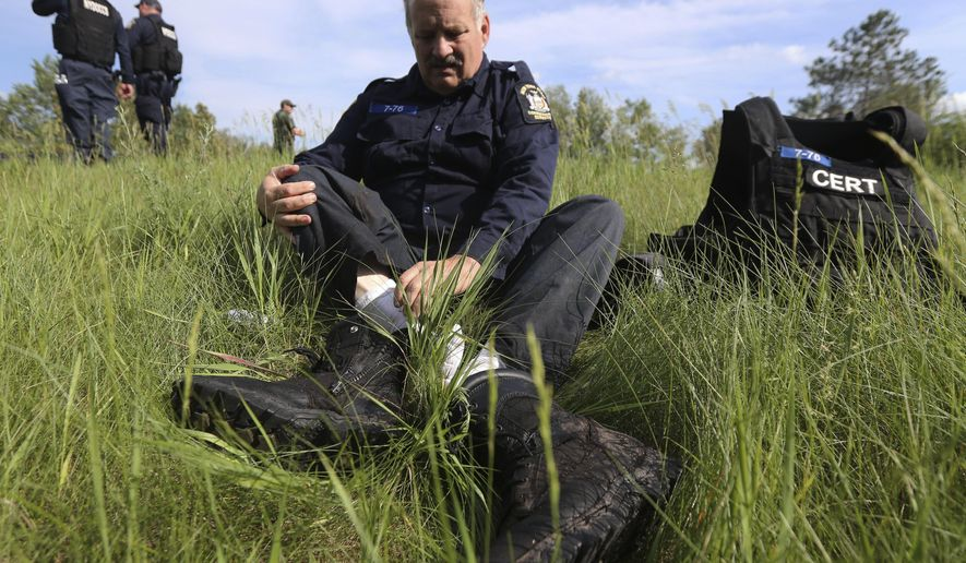 A law enforcement officer takes off his boots during a break in the search for two prisoners who escaped from the Clinton Correctional Facility on Saturday, June 13, 2015, in Saranac, N.Y. Authorities are in the eighth day of searching for David Sweat and Richard Matt, two killers who used power tools to cut their way out of the prison in northern New York. (AP Photo/Mike Groll)