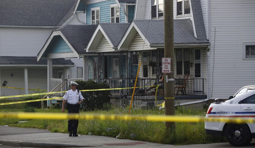 Columbus police officer stands at the scene after multiple people were killed and a teenage girl injured in a shooting inside a home Saturday, June 13, 2015, in Columbus, Ohio. A police dispatcher confirmed that four people were found dead in the Columbus home's basement. Sgt. David Sicilian of the homicide squad told The Columbus Dispatch that police feared the injured teen's safety may be in danger with a suspect on the loose. (Tom Dodge/The Columbus Dispatch via AP)