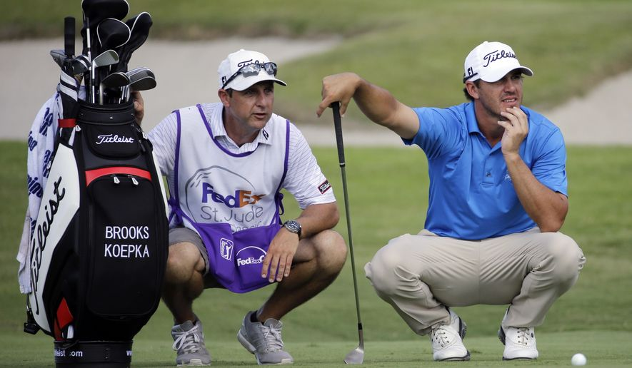 Brooks Koepka, right, studies the 16th green with his caddie in the second round of the St. Jude Classic golf tournament Friday, June 12, 2015, in Memphis, Tenn. (AP Photo/Mark Humphrey)