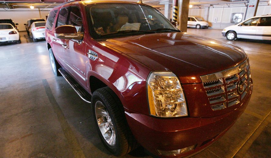 FILE - In this Sept. 5, 2006, file photo, the Cadillac Escalade, according to authorities, in which polygamous church leader Warren Jeffs was riding in when he was apprehended by authorities is shown, in the garage at the FBI offices in Las Vegas. The car and items found inside it will be auctioned off in St. George.  (Jud Burkett/The Spectrum via AP) NO SALES