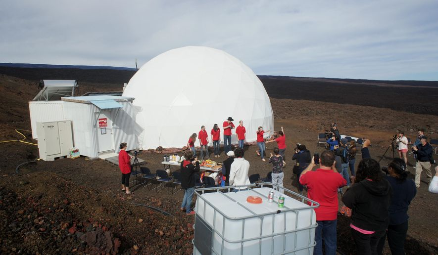 In this photo provided by the University of Hawaii at Manoa HI-SEAS Human Factors Performance Study, six scientists exit a dome that they lived in as part of an isolated existence to simulate life on a mission to Mars, on the bleak slopes of dormant volcano Mauna Loa near Hilo on the Big Island of Hawaii, Saturday, June 13, 2015. The scientists who took part of a human performance study funded by NASA, stepped outside the dome at 8,000 feet elevation to feel fresh air on their skin Saturday, the first time they'd ventured out without donning a space suit in eight months. (Ryan Ogliore/University of Hawaii at Manoa via AP) MANDATORY CREDIT