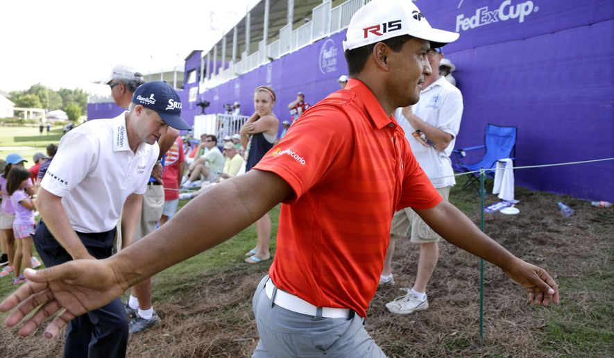Fabian Gomez, of Argentina, greets fans as he leaves the 18th green during the third round of the St. Jude Classic golf tournament Saturday, June 13, 2015, in Memphis, Tenn. Gomez finished the round tied for first place at 9-under-par 201. At left is his playing partner, Russell Knox, of Scotland. (AP Photo/Mark Humphrey)